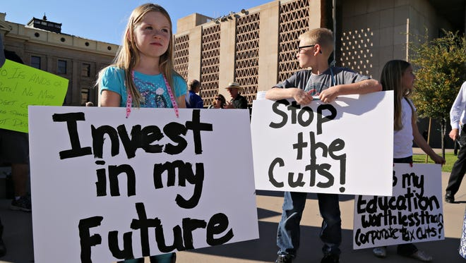 Ashley, Justin and Natalie Kistner hold signs during a protest against education budget cuts at the state capital in 2015.