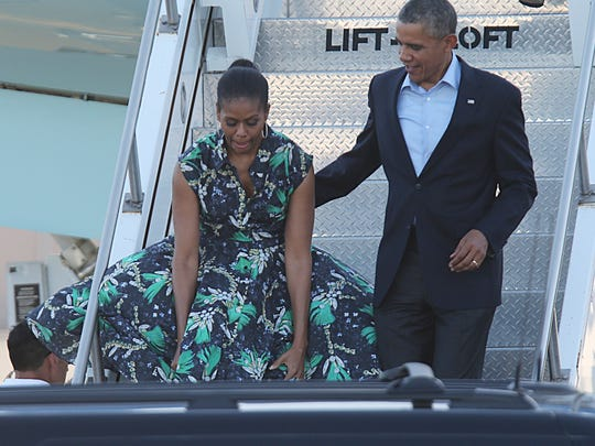 First Lady Michelle Obama reaches down after a wind gust billowed her dress as she and President Barack Obama exit Air Force One at the Palm Springs International Airport, Friday, June 13, 2014.