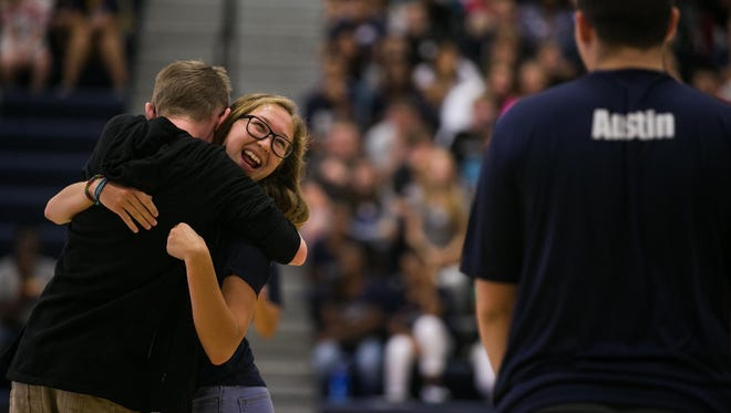 Senior Bella Ostby, 17 from Des Moines, hugs incoming freshman Mitch Majure, 14 from Des Moines as the pair try to pop a balloon between them during a game at freshman orientation at Theodore Roosevelt High School on Thursday, August 20, 2015. The orientation day is part of the new Link Crews program which helps the incoming freshman adjust to life in high school.