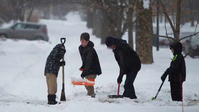 File photo: Peter, Ian, Tim, and William McNamara shovel snow in their driveway to their home on Seneca Parkway.