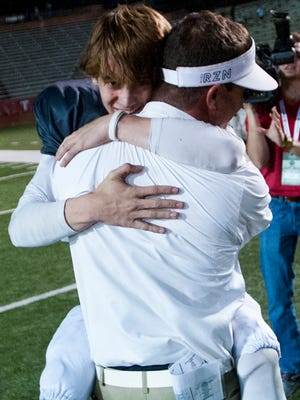 Autauga Academy quarterback Tripp Carr hugs his father Bobby Carr after Autauga defeated Escambia during the AISA Football Tripleheader Championship at Veterans Memorial Stadium on the Troy University campus in Troy, Ala. on Friday November 18, 2016.