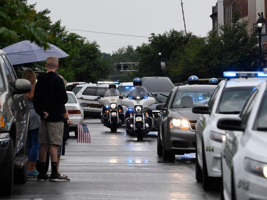 People pay their respects to fallen Dickson County officer Sgt. Daniel Baker on a downtown Dickson street as a police processional escorts his casket to Taylor Funeral Home in Dickson on Thursday, May 31, 2018.
