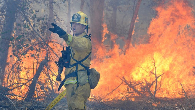 A San Bernardino County firefighter yells for more water while battling a fire along the Mojave River in Victorville, Calif.