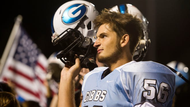 Gibbs football player Skyler Merrell raises his helmet after his team's win against Halls at Gibbs' homecoming game on Friday, Sept. 30, 2016, at Gibbs High School. In February Skyler was involved in a car accident with his teammate Clay Church and his two brothers Austin Merrell, 22, and Andy Merrell,14. Both Austin and Andy were killed in the crash.