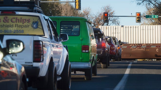 Evening traffic waits to proceed northbound on Lemay Avenue as a train crosses Lemay south of Vine Drive in October. The city of Fort Collins is considering whether to build an overpass of the railroad switch yard that runs along Vine as part of a road realignment to ease congestion.