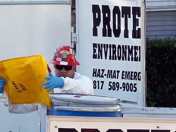 A hazmat worker with Protect Environmental places an
