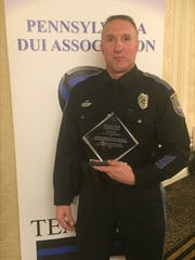 "Patrolman Scott George holds his"" Top Gun"" award, which"