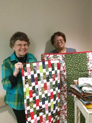 Shown is Barb Scott who yearly makes dozens of quilts for children, along with Helen Williams of the NICU ward and a cart filled with baby afghans, receiving blankets and pillowcases, as well as several Christmas themed quilts.