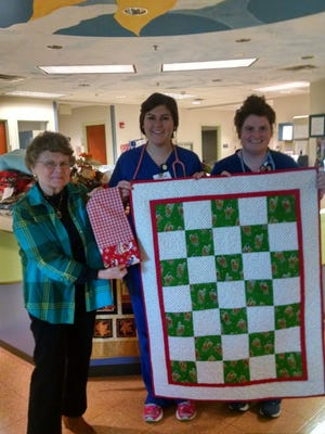 Pediatric nurses Caroline Shelley and Annaruth Branyon accept quilts and blankets, as well as holiday themed pillowcases for the children in their ward, from Barb Scott, at left.