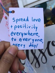 "A University of Delaware student writes a positive message during a Muslim Student Association activity: ""Spread love + positivity everywhere to everyone every day."""
