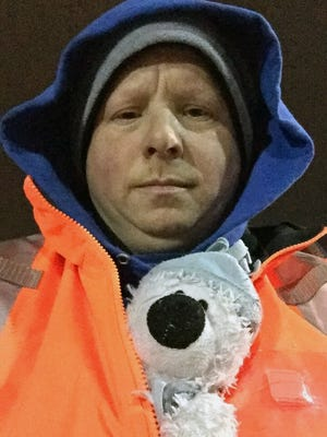 This December 2016 photo provided by Steven J. Laudeman shows Laudeman with a stuffed bear named Teddy that Eleanor Dewald, 8, lost lost flying from Dallas to Detroit Metropolitan Airport.