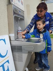 Mason Villareal and UCCE staffer Alice Escalante fill a water bottle.