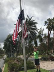 Cal Jordan replaces a torn American flag after Hurricane