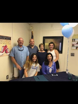 Marco Island Academy swimmer Susan Faremouth (bottom left) celebrated her signing with Lynn University in Boca Raton during a ceremony at the school Tuesday. To the right of Faremouth is her mother Stacy. In bottom row, left to right, are Susan's father Jay, uncle Mark, grandmother Carol and sister Lauren.