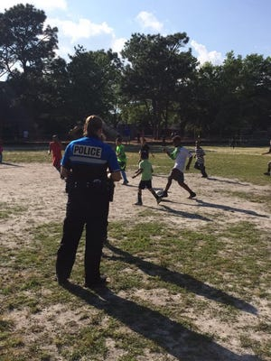 An officer stands on the sidelines as kids play soccer during an event by WPD's Police Activities League, a community policing program that aims to connect officers with Wilmington's youth.