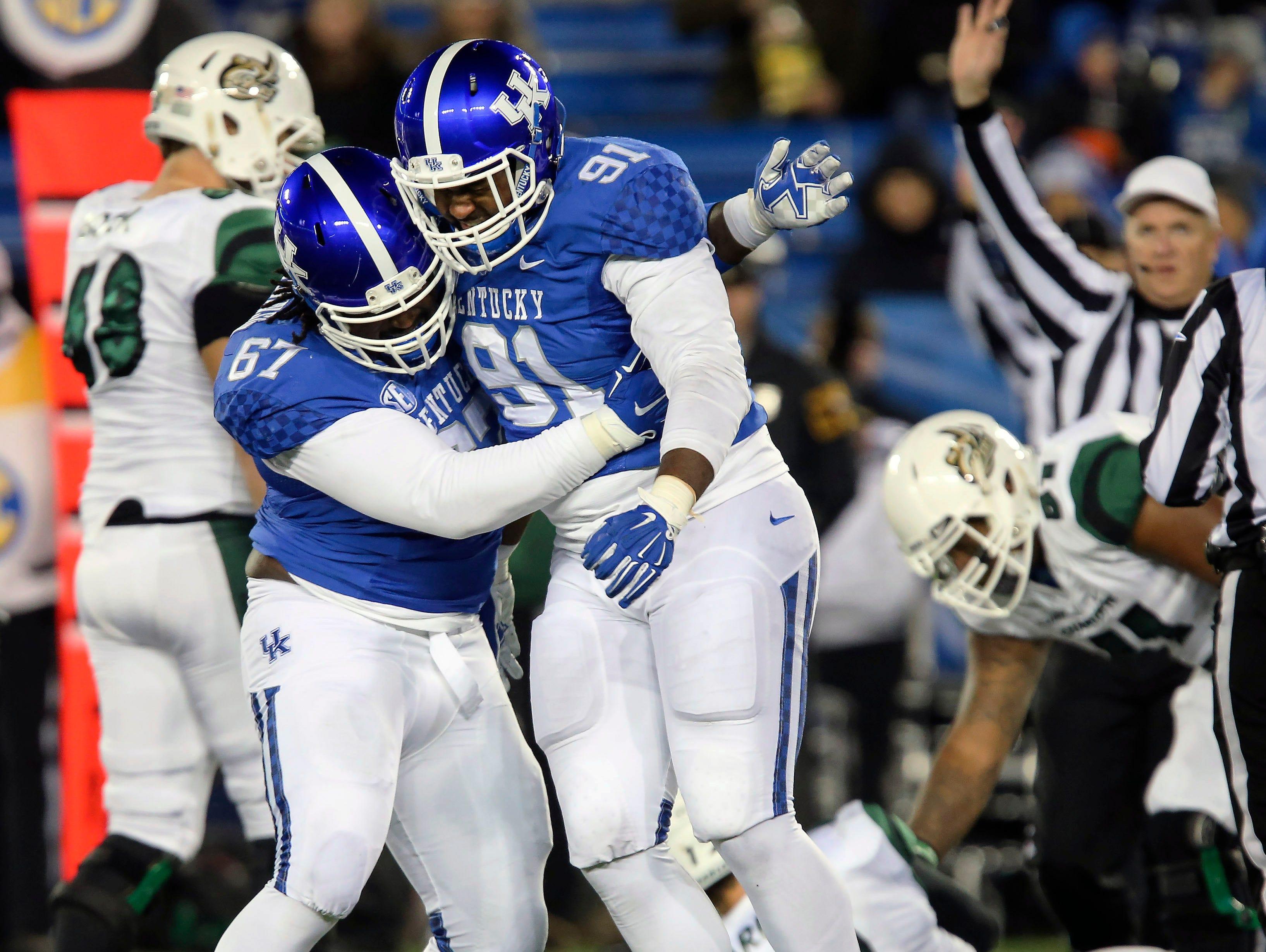 Kentucky defensive tackle Cory Johnson, left, congratulates defensive end Farrington Huguenin after he sacked Charlotte quarterback Brooks Barden during the first half of an NCAA college football game Saturday, Nov. 21, 2015, in Lexington, Ky.