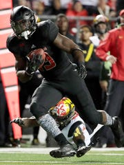 Rutgers running back Gus Edwards, front, avoids a tackle