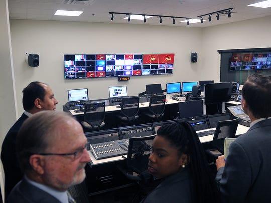 Midwestern State University regents and other officials look over the control room and adjacent studio in the broadcast lab of the new Mass Communications building during a tour Thursday.
