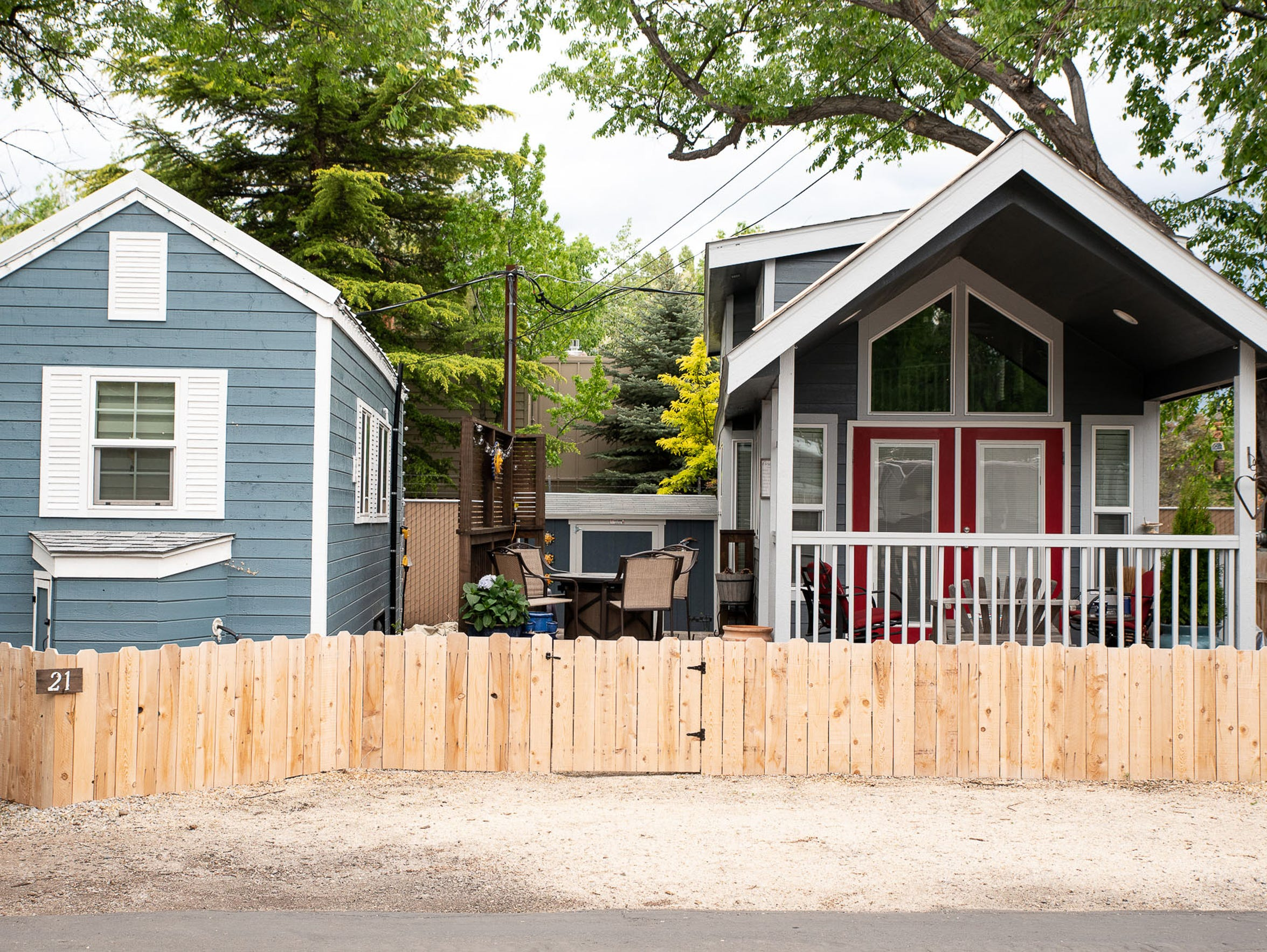 Two tiny-house style trailers sit side by side at the