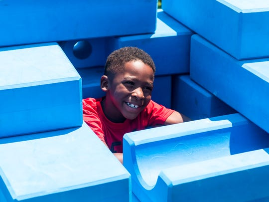 Ahmir Simmons has a block fort built around him during Millville's first Play Streets week on East Pine Street in Millville on Wednesday.