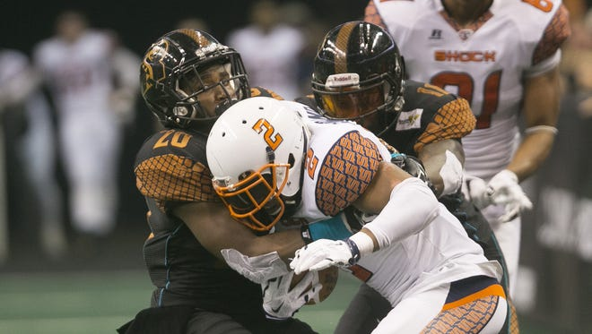 Rattlers' Jeremy Kellem and Arkeith Brown make a tackle on Shock's Jabin Sambrano during the First Round playoff game at the US Airways Center in Phoenix, AZ on Aug. 15, 2015.