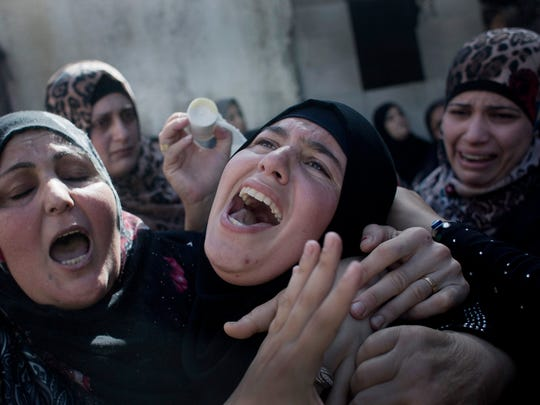 Palestinian Fatema Masalmeh, center, the wife of slain Udai Masalmeh, 24, mourns during his funeral at the family house in the West Bank village of Beit Awa, Hebron, Wednesday, Oct. 21, 2015. The 24 year old Palestinian was fatally shot near the village of Beit Awa after lightly injuring an Israeli army officer with a knife, according to a statement from the military. The incident reportedly occurred during Palestinian protests the army described as violent. (AP Photo/Nasser Nasser)