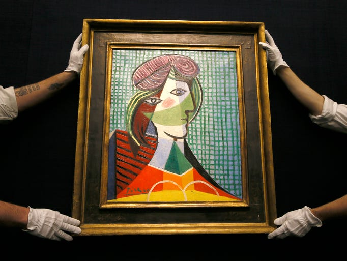 Sotheby's employees adjust a painting by Pablo Picasso