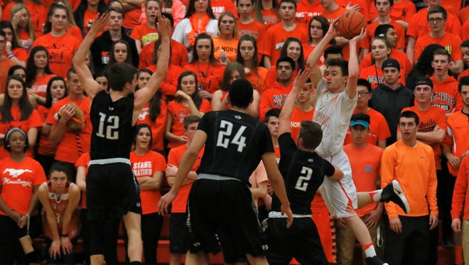 Northville's Kevin Morrissey (4) looks to throw the ball in over a wall of Plymouth defenders. In the background is Northville's orange-clad student section.