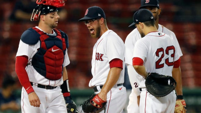 Red Sox pitcher Marcus Walden, center, reacts between teammates Kevin Plawecki, left, Xander Bogaerts, behind, and Michael Chavis (23) as manager Ron Roenicke comes to the mound for a pitching change during the game against the Tampa Bay Rays on Monday.