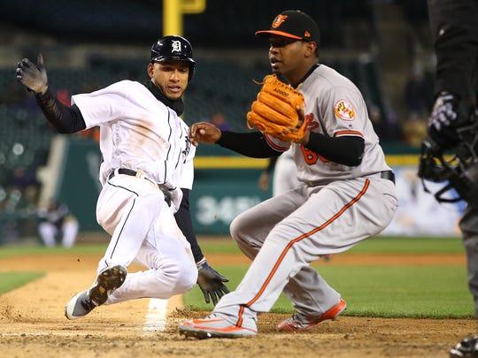 Victor Reyes slides into home plate past Mychal Givens,