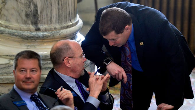 Rep. Art Wittich, R-Bozeman, sitting, chats with Sen. Ed Buttrey, R-Great Falls, on the House Floor during the 2015 legislative session. Wittich has been a key opponent to Buttrey's Medicaid expansion bill and argued it should not be blasted out of his House committee without a supermajority vote.