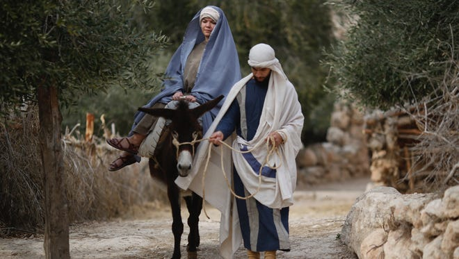 Christian actors portray Joseph and Mary during a re-enactment of a Nativity scene of the journey to Bethlehem as part of Christmas festivities at the Nazareth Village, northern Israel, Thursday, Dec. 21, 2017.
