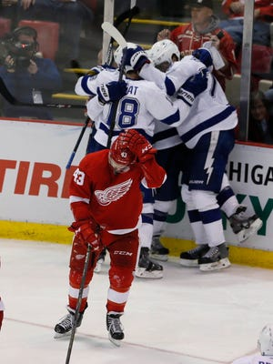 Detroit Red Wings' Darren Helm skates away as   Tampa Bay Lightning players celebrate their overtime goal for a 3-2 win in Game 4 on April 23, 2015 at Joe Louis Arena. The series is tied 2-2 with Game 5 on Saturday in Tampa Bay.