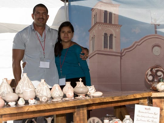 Hector Gallegos and his daughter Paula of Mata Ortiz, Chihuahua, Mexico, show traditional pottery motifs and  forms  at  the new Artistas del Camino Real feature at the recent Doña Ants Council Renaissance ArtsFaire at Young Park. Las Cruces artist Bob Diven created silk-screened backdrops with historical scenes for the New Mexico True feature.