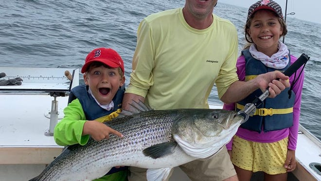 Marty Tracy, with children Kate and Jonah, caught and released striped bass last week while charter fishing the North Rip with Block Island Fish Works.