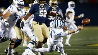 University of Memphis quarterback Riley Ferguson (middle) makes an awkward pass against the Navy defense during fourth-quarter action at Navy-Marine Corps Memorial Stadium in Annapolis, Maryland. Ferguson was called down on the play, causing a 13-yard loss.