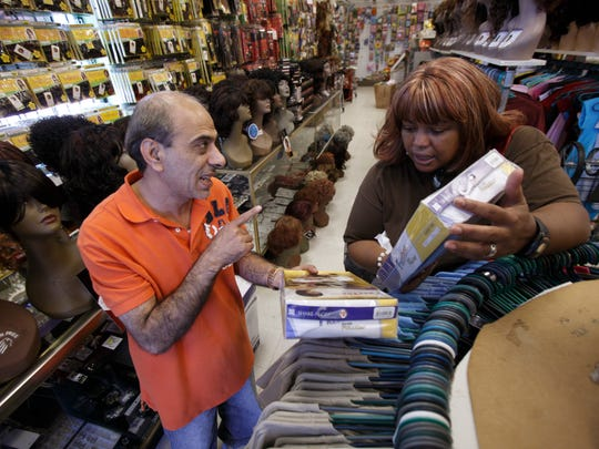 Salah Jaber, owner of More 4 Less Beauty Supply, helps