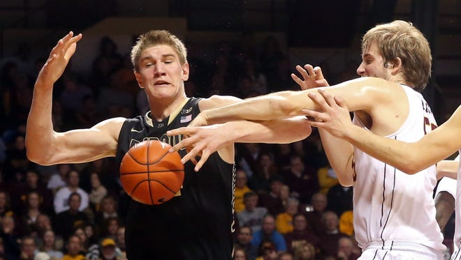 Minnesota's Elliott Eliason knocks the ball away from Purdue's Isaac Haas, left, in the first half of an NCAA college basketball game, Saturday, Feb. 7, 2015, in Minneapolis.