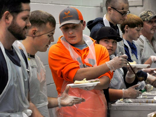 Mason Cunningham hands a plate to Richard Lowry as they serve food during the Feast of Sharing Tuesday night at the Abilene Civic Center. The two volunteers are airmen at Dyess.