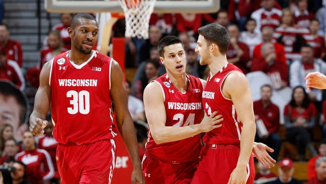 Bronson Koenig (center) celebrates one of his 5 three-pointers with Vitto Brown and  Zak Showalter.