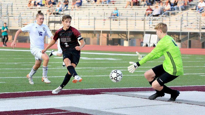 Buhler's Kayden Polk (2) kicks the ball past Circle's goal keeper Grant Ledbetter (00) for a goal during their game Tuesday evening. Buhler defeated Circle 11-0 in the first half.