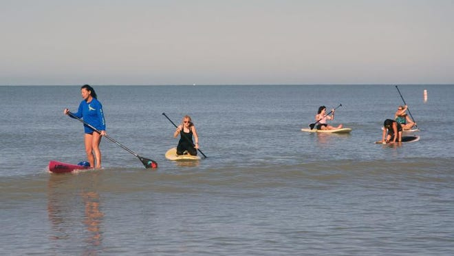 Kat Lucchesi (in blue) leads a group of paddleboarders in a boot camp type of session in the waters off Delnor-Wiggins State Park.