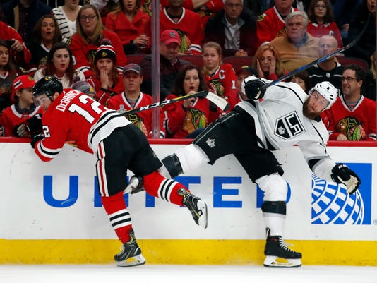 Chicago Blackhawks right wing Alex DeBrincat (12) collides with Los Angeles Kings defenseman Jake Muzzin (6) during the first period of an NHL hockey game Monday, Feb. 19, 2018, in Chicago. (AP Photo/Jeff Haynes)