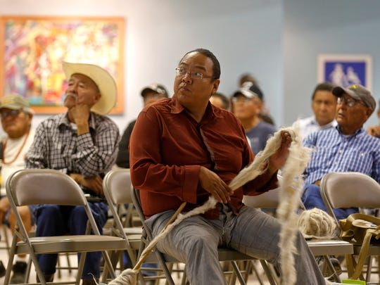 Shiprock resident Zefren Anderson and fellow community members listen to a presentation on the possible regionalization of Navajo government Wednesday at the Shiprock Chapter house.