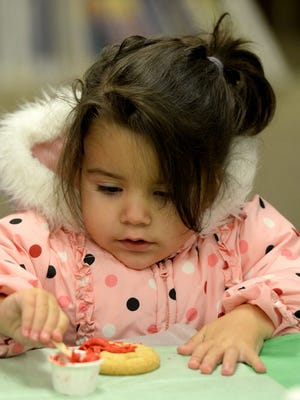 Ava Stephens decorates a cookie at the Centerville's library during Christmas in Centerville.