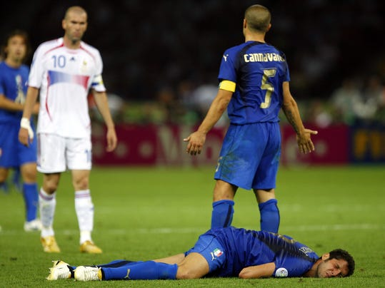 FILE - In this Sunday, July 9, 2006, file photo, France's Zinedine Zidane, left, looks on as Italy's Marco Materazzi lies injured, and Italy's Fabio Cannavaro reacts, during extra time in the World Cup final soccer match between Italy and France, at the Olympic Stadium, in Berlin. On this day: Zidane is sent off minutes before the end of the final after head-butting Italy defender Materazzi. Italy wins ensuing penalty shoot-out to claim its fourth World Cup. (AP Photo/Jasper Juinen, File)