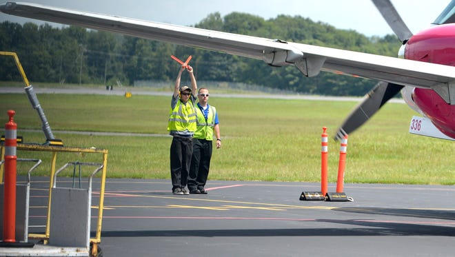 Members of the ground crew help a United Airways flight, operated by Silver Airways, in parking itself outside the passenger terminal at Shenandoah Valley Regional Airport after its arrival from Dulles International Airport on Wednesday, Aug. 21, 2013.