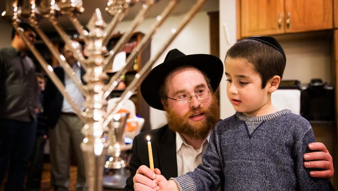 Rabbi Yossi Bendet lights the menorah candles with his son Mendel, 4, in their home in Bloomington,  Wednesday, Dec. 13.