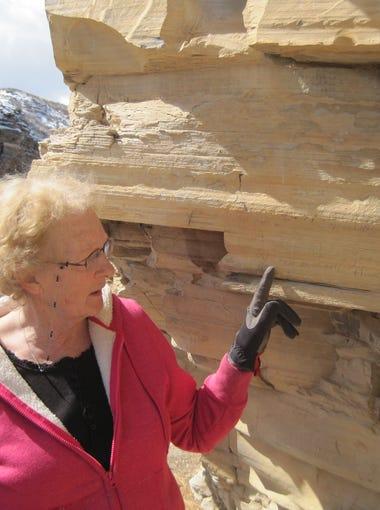 Macie Ahlgren points to historical graffiti at Bear