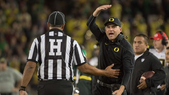 November 14, 2015; Stanford, CA, USA; Oregon Ducks head coach Mark Helfrich (right) argues with a referee during the fourth quarter against the Stanford Cardinal at Stanford Stadium. The Ducks defeated the Cardinal 38-36. Mandatory Credit: Kyle Terada-USA TODAY Sports